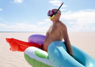 Man on beach with floaties